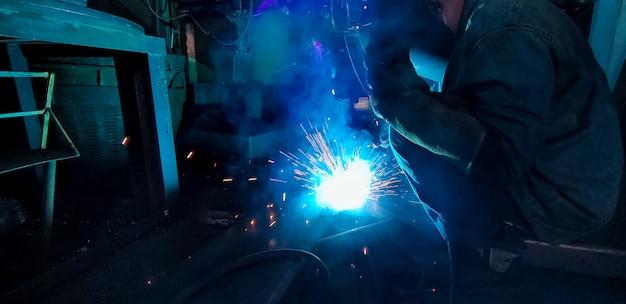 Saldatore di metallo di saldatura con saldatrice ad arco di argon e ha scintille di saldatura. un uomo indossa una maschera da saldatura e guanti protettivi. sicurezza negli ambienti di lavoro industriali. saldatore che lavora con sicurezza. industria siderurgica.