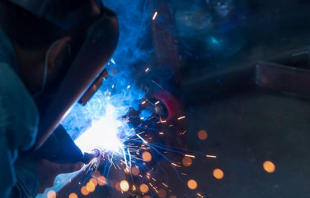 Saldatore di metallo di saldatura con saldatrice ad arco di argon e ha scintille di saldatura. un uomo indossa una maschera da saldatura. sicurezza negli ambienti di lavoro industriali. saldatore che lavora con sicurezza. tecnologia dell'industria siderurgica.
