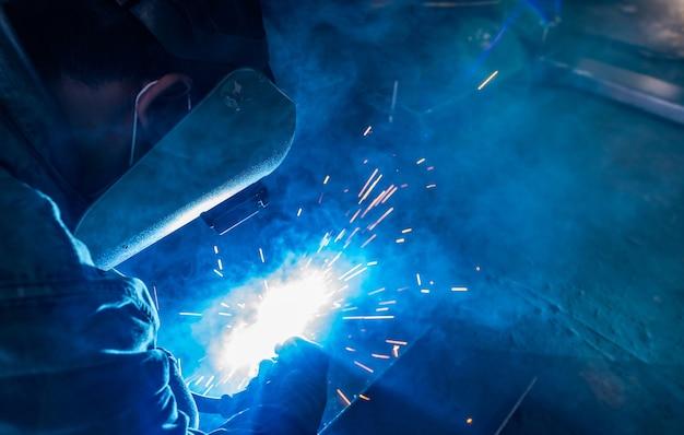 Saldatore che salda il metallo con la saldatrice e ha scintille di saldatura l'uomo indossa maschera e guanti per saldatura welding