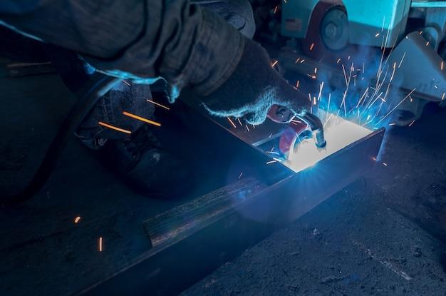 Saldatore saldatura metallo con saldatrice e saldatura scintille sicurezza sul posto di lavoro industriale