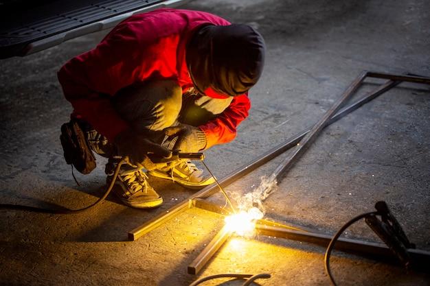 Il saldatore esegue il processo di saldatura presso l'officina industriale, le mani con lo strumento nel telaio. Foto Premium