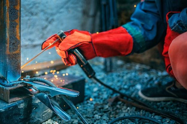 Il saldatore salda un tubo metallico con saldatura elettrica, tiene un elettrodo tra le mani