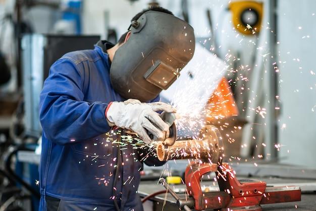 Saldatore al lavoro, uomo di saldatura maschera che macina un tubo metallico sul banco di lavoro industriale