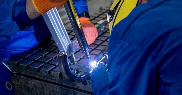 Saldatore che lavora in una fabbrica di acciaio con saldatura ad argon.