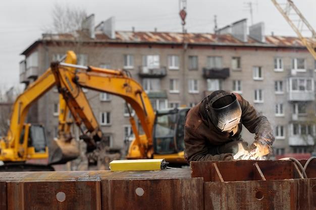 Il saldatore lavora alla costruzione di una costruzione monolitica dell'edificio residenziale