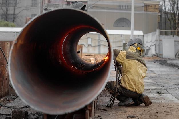 Il saldatore lavora alla costruzione di una costruzione monolitica dell'edificio residenziale Foto Premium