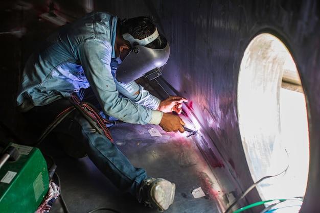 Il metallo riparato maschio del lavoratore dell'argon dell'arco di saldatura sta saldando l'olio del serbatoio della costruzione industriale delle scintille all'interno di spazi ristretti.