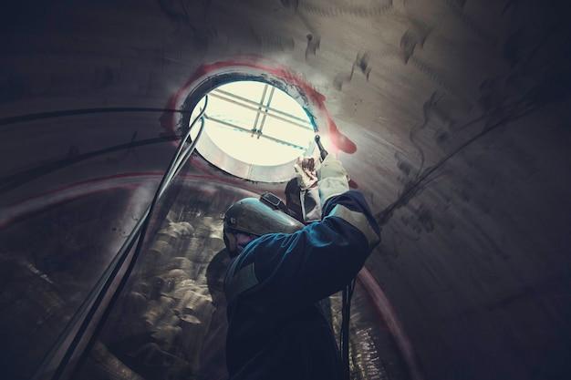 Saldatura arco argon lavoratore maschio metallo riparato sta saldando scintille costruzione industriale serbatoio parte tombino olio inossidabile all'interno di spazi ristretti c'è un guardiano fuori.