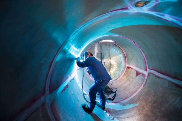 Il metallo riparato maschio del lavoratore dell'argon dell'arco di saldatura sta saldando l'olio inossidabile del serbatoio della costruzione industriale delle scintille all'interno di spazi ristretti.