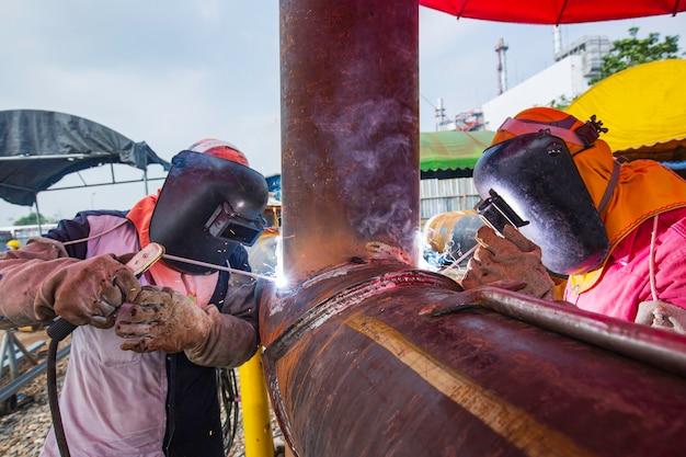 Saldatura maschio di due lavoratori in metallo fa parte della costruzione di condutture di ugelli per macchinari petrolio e gas