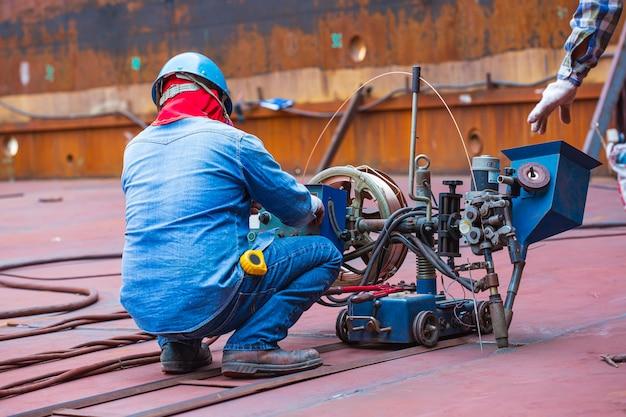 Saldatura di controllo dell'operaio maschio che affiora del rotolo di acciaio della piastra di fondo del serbatoio mediante processo di saldatura ad arco sommerso di scorie.