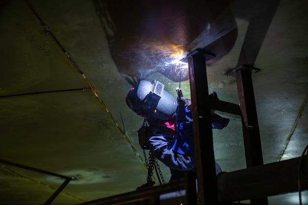 L'arco metallico del lavoratore maschio di saldatura fa parte del serbatoio di stoccaggio del petrolio e del gas della costruzione di condutture dell'ugello del serbatoio del macchinario all'interno di spazi ristretti.