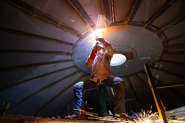 La saldatura ad arco di metallo per operai è parte del serbatoio per la costruzione di serbatoi di petrolio e gas all'interno di spazi ristretti.