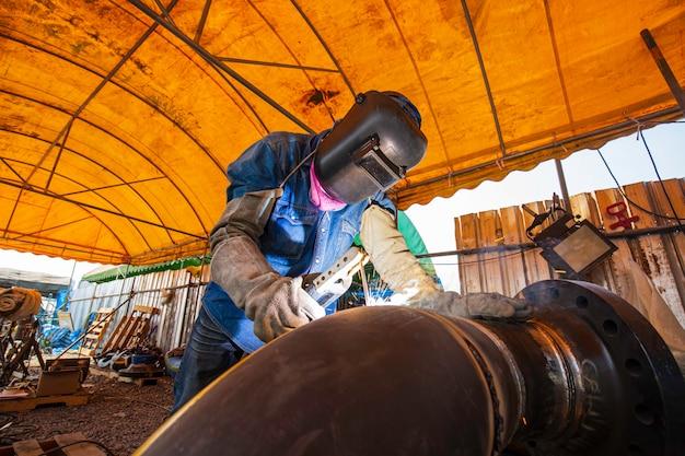 La saldatura del metallo del lavoratore maschio fa parte della costruzione di condutture di ugelli per macchinari petrolio e gas