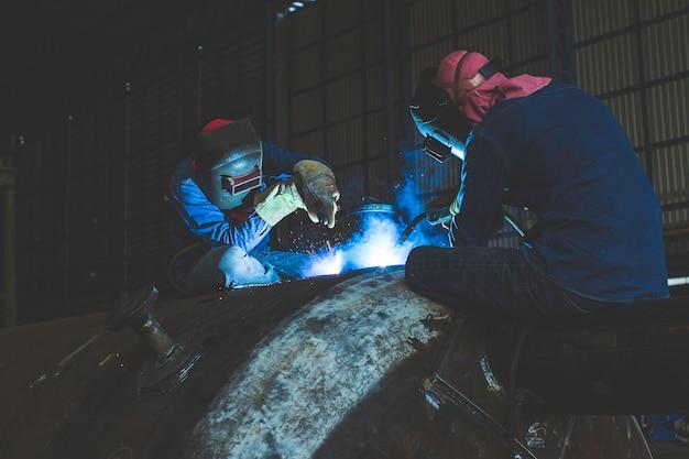 La saldatura del metallo dei lavoratori di sesso maschile fa parte della costruzione di condutture di ugelli per macchinari petrolio e gas