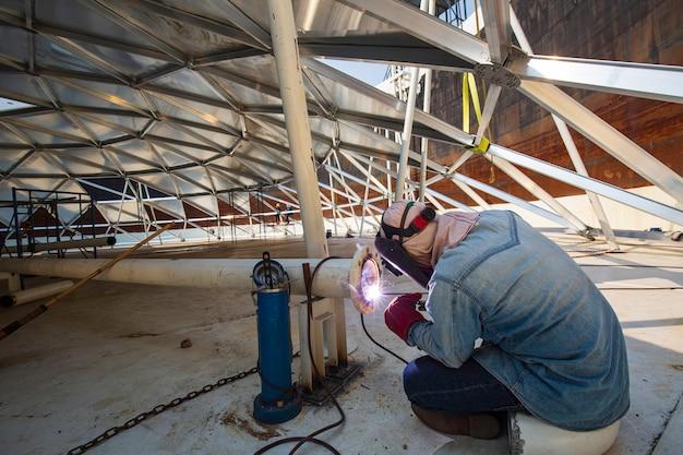 La saldatura del metallo del lavoratore di sesso maschile fa parte dello spazio limitato in alluminio della cupola del serbatoio di stoccaggio della conduttura dell'ugello del macchinario.