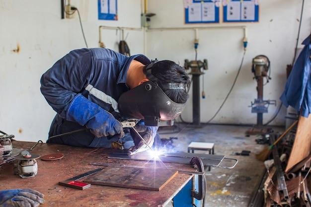La saldatura del metallo del lavoratore di sesso maschile fa parte del garage di riparazione dei macchinari