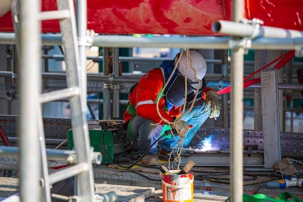 La saldatura del metallo del lavoratore di sesso maschile fa parte del garage di riparazione dei macchinari Foto Premium