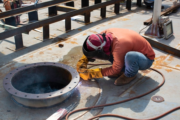 La saldatura del metallo del lavoratore maschio fa parte del serbatoio di stoccaggio del petrolio e del gas della costruzione di condutture dell'ugello del serbatoio del macchinario all'interno di spazi ristretti. Foto Premium