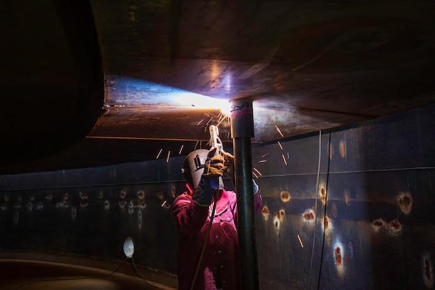 La saldatura del metallo del lavoratore maschio fa parte del serbatoio di stoccaggio del petrolio e del gas della costruzione di condutture dell'ugello del serbatoio del macchinario all'interno di spazi ristretti.