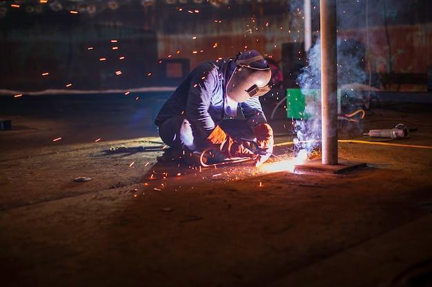 La saldatura del metallo del lavoratore maschio fa parte del serbatoio di stoccaggio del petrolio e del gas della costruzione del fondo della piastra del serbatoio del macchinario all'interno di spazi ristretti.
