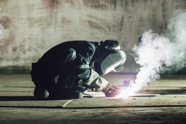 La saldatura del metallo dell'operaio maschio fa parte del serbatoio di stoccaggio del petrolio e del gas della costruzione del fondo della piastra del serbatoio del macchinario all'interno di spazi ristretti. Foto Premium