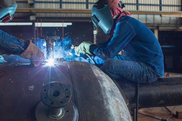 La saldatura di due lavoratori di sesso maschile in metallo fa parte della costruzione di serbatoi di ugelli per macchinari petrolio e gas