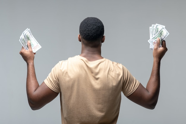 Benessere. vista posteriore del forte uomo dalla pelle scura con banconote in mani alzate in piedi su sfondo chiaro