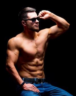 Beh, costruisci un bell'uomo senza camicia in posa in studio