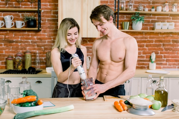 Basamento bello ben fatto dell'uomo al tavolo in cucina. aiuta la sua bella ragazza a mescolare frullati con cibi sani. coppia felice, stile di vita sano, cibo sano
