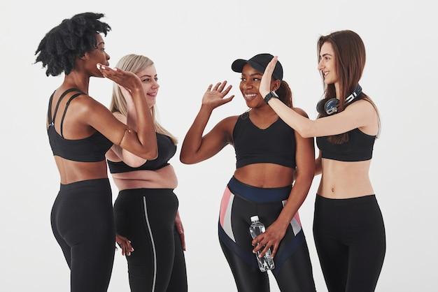 Ben fatto, dopo l'allenamento. gruppo di donne multietniche in piedi