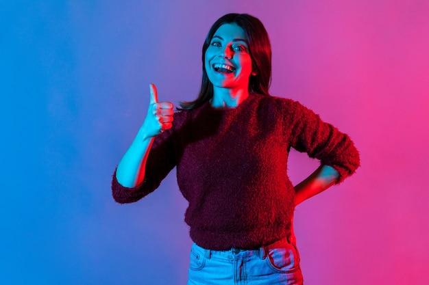 Bravo, buon lavoro! ritratto di luce al neon di gioiosa donna bruna che mostra i pollici in su come