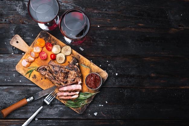 Bistecca di maiale ben cotta su un tagliere. due bicchieri di vino rosso secco. cena per due posti per il testo