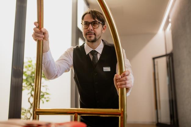 Portiere barbuto ben vestito in occhiali che spinge il carrello con i bagagli mentre si muove lungo il corridoio all'interno dell'hotel