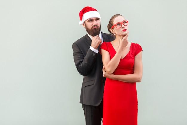 Uomo d'affari e donna ben vestiti che guardano lontano, toccano il mento e pensano. foto in studio