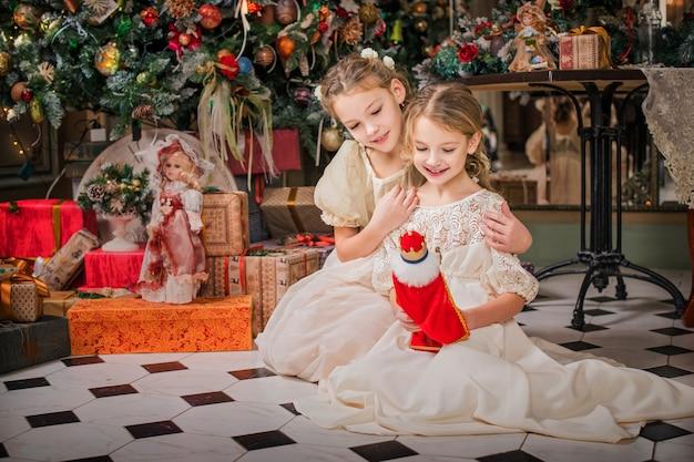 Bambine ben vestite con bei vestiti che guardano i regali sotto l'albero di natale