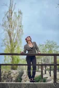 Ragazza ben vestita in posa su un ponte.