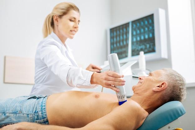Ospedale ben attrezzato. piacevole terapista femminile allegro seduto vicino al suo paziente e utilizzando attrezzature moderne mentre controlla la sua salute