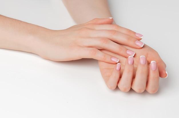Mani femminili ben curate con il manicure su bianco