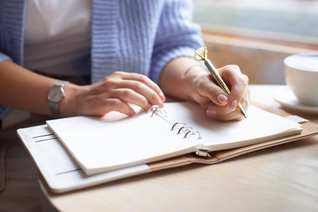 Mano di donna ben curata che tiene penna d'oro e scrivere note con penna d'oro in taccuino mentre beve latte blu accanto alla finestra giornalista freelance che lavora da casa. pianificazione del concetto futuro. copia spazio