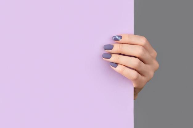 Mano di donna ben curata che tiene bandiera di carta viola su sfondo grigio. modello di salone di bellezza ufficio affari.