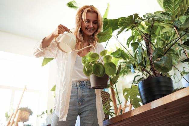 Bene e donna felice vestita in abiti casual che innaffia le sue piante d'appartamento a casa. ritratto caldo di un appartamento e di una donna moderni.