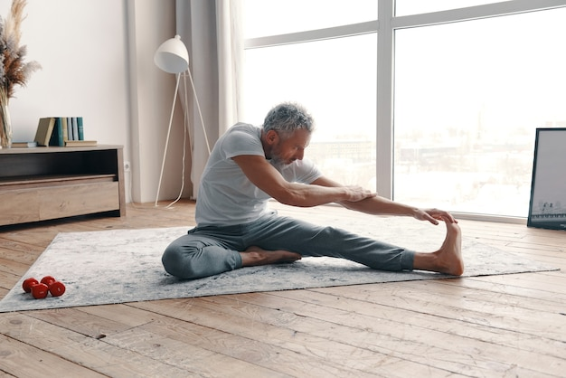 Uomo anziano ben modellato in abbigliamento sportivo che si allunga mentre è seduto sul pavimento vicino alla finestra di casa