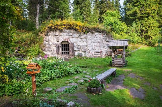 Un pozzo e una cantina in pietra nel giardino botanico delle isole solovetsky tra il verde delle piante