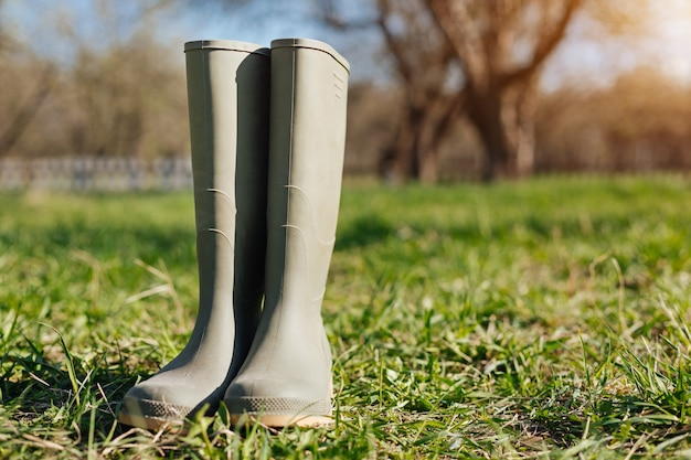 Stivali da pioggia per un lavoro in giardino all'aperto in piedi nel cortile di una casa di campagna in primavera