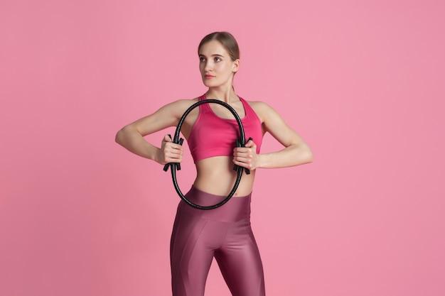 Benessere. bella giovane atleta femminile che si esercita in studio, ritratto rosa monocromatico