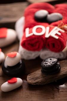 Documentazione del benessere il giorno di san valentino con asciugamani e pietre da vicino
