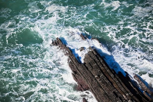 Costa occidentale dell'oceano del portogallo. scogliera e surf. scatto vignettato