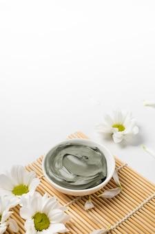 Argilla cosmetica bagnata blu per maschera per la cura del viso su stuoia di bambù