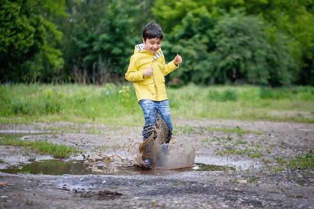 Un bambino bagnato sta saltando in una pozzanghera. divertimento per strada.